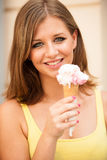 Attractive young woman eating ice cream Stock Photos