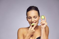 Attractive young woman eating a slice of cucumber Stock Image