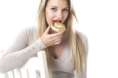 Attractive Young Woman Eating a Toasted Crumpet Royalty Free Stock Images