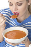 Attractive Young Woman Eating Tomato Soup Stock Images
