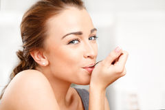 Attractive young woman eating yogurt. At home Royalty Free Stock Photography