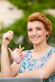Attractive young woman eats ice cream outdoors Royalty Free Stock Images
