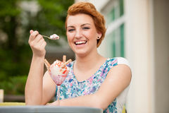 Attractive young woman eats ice cream outdoors Stock Photography