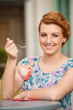 Attractive young woman eats ice cream outdoors Royalty Free Stock Photos