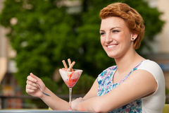 Attractive young woman eats ice cream outdoors Stock Photo