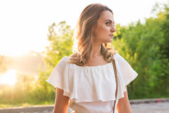 Attractive young woman enjoying her time outside in park with sunset in background Stock Photos