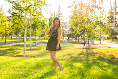 Attractive young woman enjoying her time outside in park with sunset in background Royalty Free Stock Photo