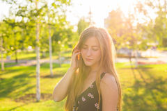 Attractive young woman enjoying her time outside in park with sunset in background Stock Photo