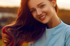 Attractive young woman enjoying her time outside in sunset park. Model girl with magnificent long color hair posing outdoor. Beauty, fashion concept. Girl in royalty free stock photo
