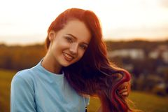 Attractive young woman enjoying her time outside in sunset park. Model girl with magnificent long color hair posing outdoor. Beauty, fashion concept. Girl in stock photography