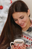 Attractive young woman enjoying hot drink on Christmas tree back Royalty Free Stock Photos