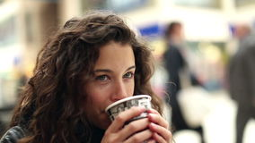 Attractive young woman enjoying a hot drink stock footage