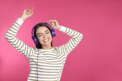Attractive young woman enjoying music in headphones on color background stock photography