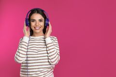 Attractive young woman enjoying music in headphones on color background stock images