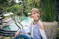 Attractive young woman in ethnic style look posing near the swimming pool, portrait. Tropical island Bali, luxury resort Stock Photos