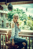 Attractive young woman in ethnic style look posing in tropical restaurant, portrait. Tropical island Bali, luxury resort Stock Photo