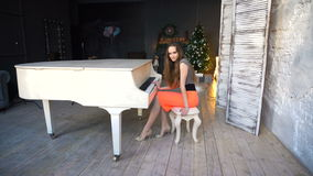 Attractive young woman in evening dress sitting at the white grand piano stock video