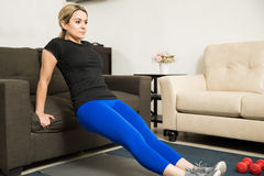 Attractive young woman exercising at home. Beautiful young woman exercising at home and doing tricep dips on a couch Stock Image