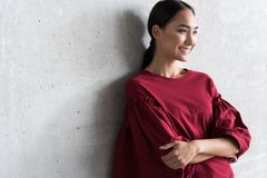 Attractive young woman is expressing gladness. Successful and confident. Positive elegant asian girl is leaning on wall with crossed arms and looking aside with stock photo