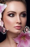Attractive young woman face with flowers. Professional Make-up. Makeup Royalty Free Stock Photo