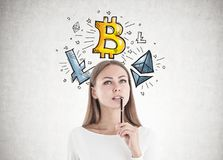 Attractive caucasian woman thinking cryptocurrency. Attractive young woman with fair hair wearing white is holding a pen near her full lips, looking up and Royalty Free Stock Photography