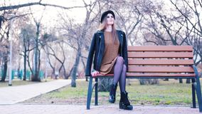 Attractive young woman in fashion dress, black hat, ankle boots and leather jacket sitting alone on the bench in park in stock footage