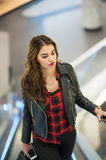 Attractive young woman fashion shot in mall. Beautiful fashionable young girl in black leather jacket on escalators in mall Stock Photo