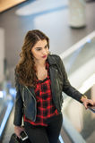 Attractive young woman fashion shot in mall. Beautiful fashionable young girl in black leather jacket on escalators in mall Royalty Free Stock Image