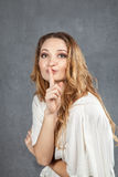 Attractive young woman with finger on lips Stock Photography