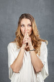 Attractive young woman with finger on lips Stock Photos