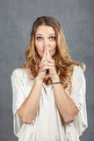 Attractive young woman with finger on lips Royalty Free Stock Photos