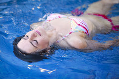 Attractive young woman floating in a swimming pool Stock Image