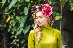 attractive young woman with floral wreath with green rainforest stock image