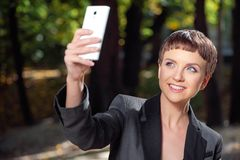 Attractive young woman in formalwear taking photo with her cellp Stock Photos