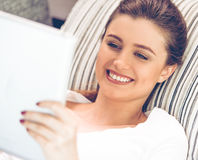 Attractive young woman with gadget. Portrait of attractive young woman in casual clothes using a digital tablet and smiling while lying on sofa at home Royalty Free Stock Photography