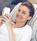 Attractive young woman with gadget. Portrait of attractive young woman in casual clothes using a smartphone and smiling while lying on sofa at home Stock Photo