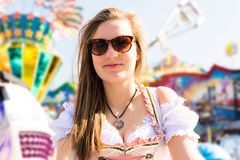Attractive young woman at German funfair Oktoberfest with traditional dirndl dress Stock Photos