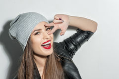 Attractive young woman is gesturing positively. Beautiful cool girl is showing peace sign near her eye. She is standing and laughing. The lady is flirting with Stock Photography
