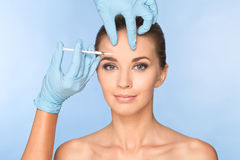 Attractive young woman gets cosmetic injection of botox. Stock Image