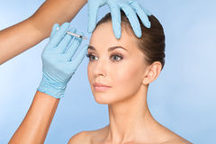 Attractive young woman gets cosmetic injection of botox. Doctors hands making an injection in face. Beauty Treatment Stock Photo