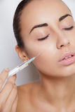 Attractive young woman gets cosmetic injection. Isolated over white background. Doctors hands making an injection in face. Beauty Treatment Stock Image