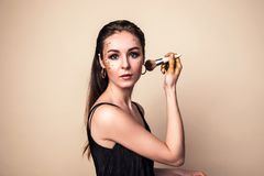 Attractive young woman with glitter make-up and brush. stock photography