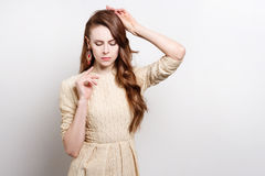 Attractive young woman in golden dress is standing, raising his hands to his face. Her gestures express doubts. She weares massive gold earrings.She has long Royalty Free Stock Photography