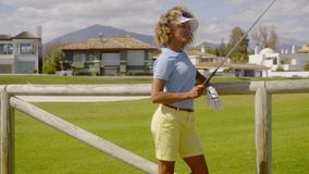 Attractive young woman golfer leaning on a fence stock footage