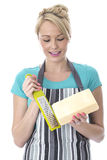 Attractive Young Woman Grating Cheese Royalty Free Stock Photography