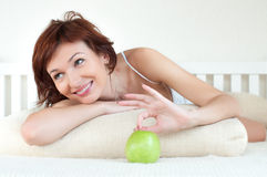 Attractive young woman with an green apple at bed Royalty Free Stock Photo