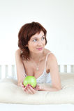 Attractive young woman with an green apple at bed Stock Photo