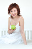 Attractive young woman with an green apple at bed Stock Photos