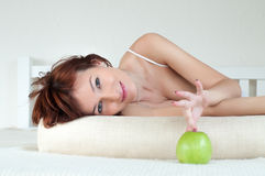 Attractive young woman with an green apple at bed Stock Photography