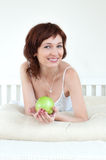 Attractive young woman with an green apple at bed Stock Images